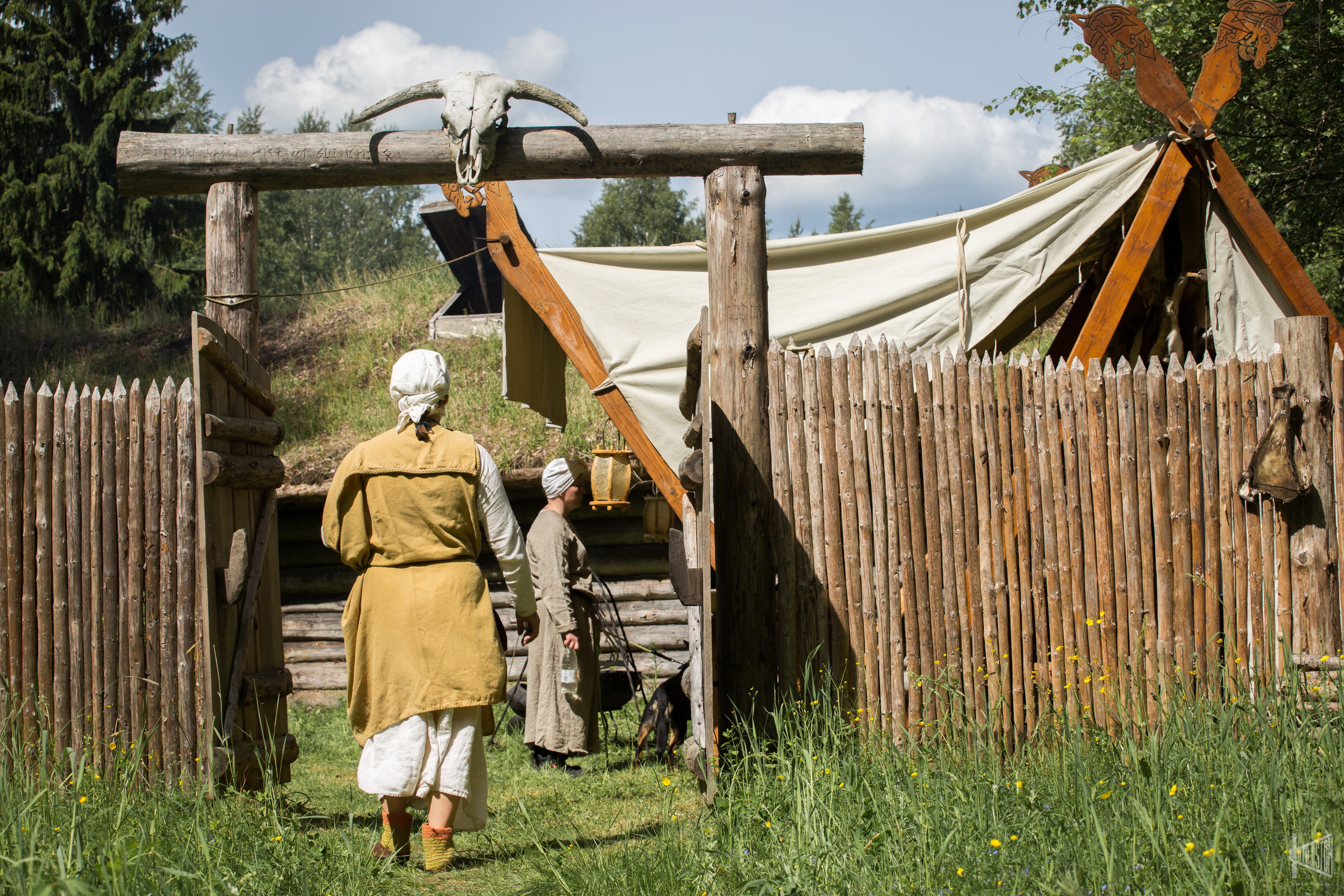 Muinaisasuun pukeutunut nainen kävelee viikinkikylän portista sisään. Portin päällä on härän pääkallo.