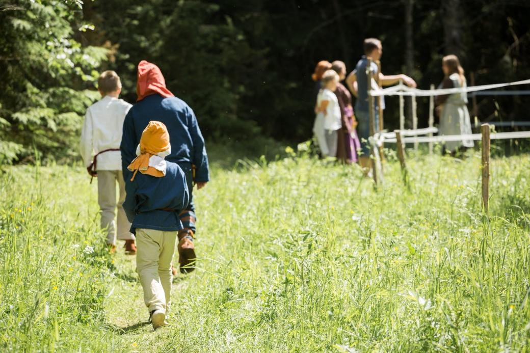 Esihistoriallisiin vaatteisiin pukeutuneet lapset kävelevät kesäisellä niityllä. Taustalla ihmisiä hevosaitauksessa.