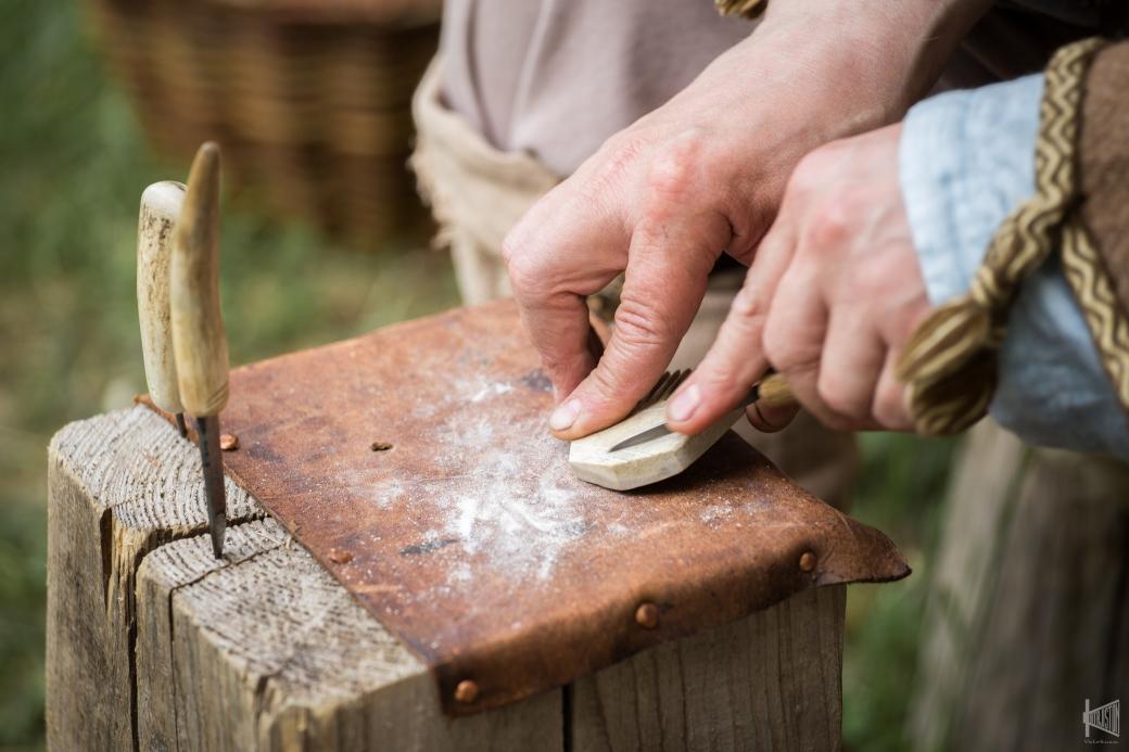Mies tekee esihistoriallisen mallin mukaista kampaa sarvesta