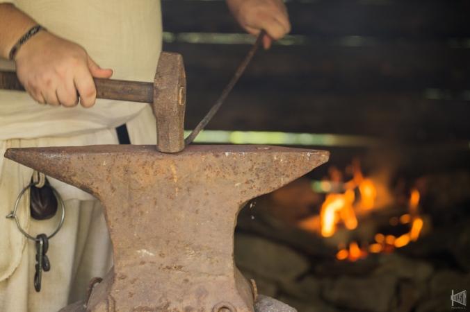 Seppä lyö rautaa alasinta vasten, taustalla palaa ahjossa tuli.